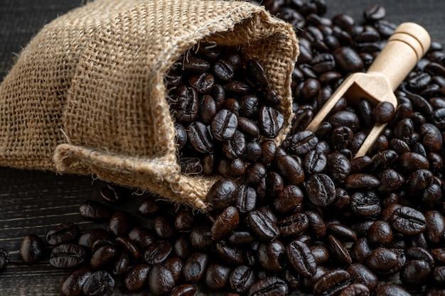 Chicchi di caffè del primo piano in borsa fatta da tela da imballaggio su superficie di legno e pala di legno che si trovano in un sacco.
