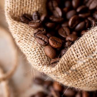Chicchi di caffè del primo piano in sacco di tela