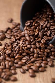 Chicchi di caffè del primo piano in tazza