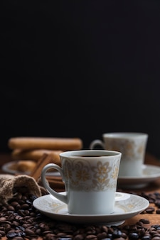 Chicchi di caffè del primo piano vicino alla tazza