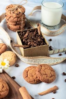 Chicchi di caffè e biscotti al burro con un bicchiere di latte su una tovaglia blu