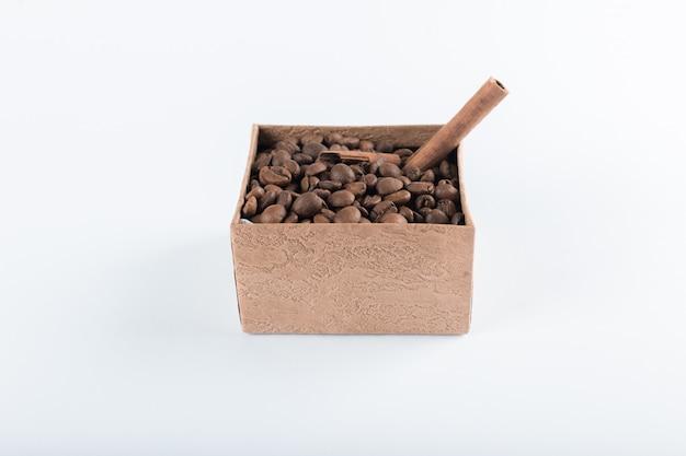Chicchi di caffè e connamons sulla scatola su bianco