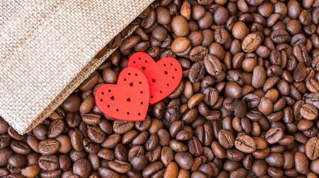 Chicchi di caffè e cuori rossi su un tavolo di legno.