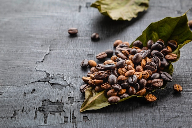 Chicchi di caffè e foglie di caffè sulla tavola di legno