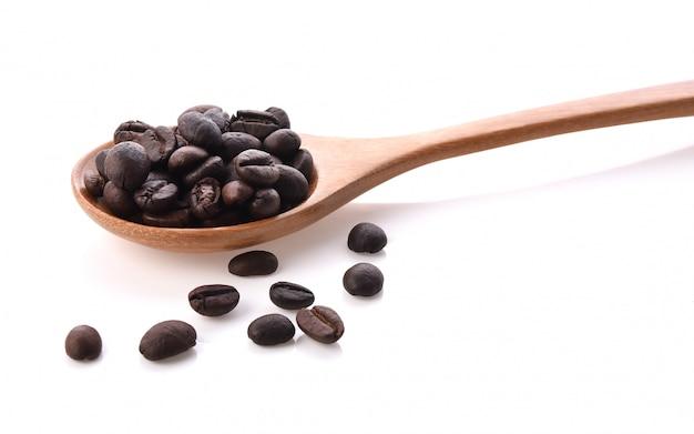 Chicchi di caffè freschi con un cucchiaio di legno isolato su sfondo bianco