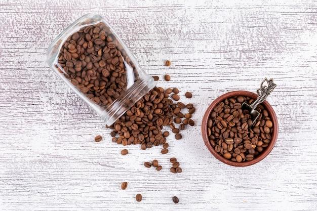 Chicchi di caffè in barattolo e piatto di vetro sulla tavola bianca
