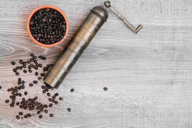 Chicchi di caffè in ciotola e macinacaffè