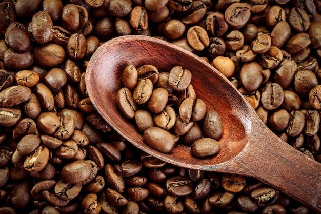 Chicchi di caffè in cucchiaio marrone su tela di sacco.
