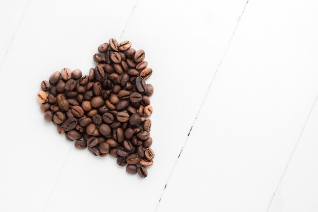 Chicchi di caffè in forma di cuore su fondo di legno bianco