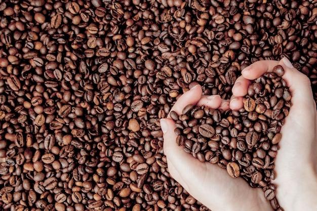 Chicchi di caffè in palme dell'uomo nella forma di un cuore sul fondo del caffè