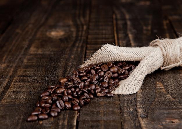 Chicchi di caffè in panno di tela sul bordo di legno