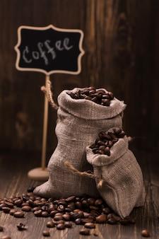 Chicchi di caffè in sacchetti di juta su legno