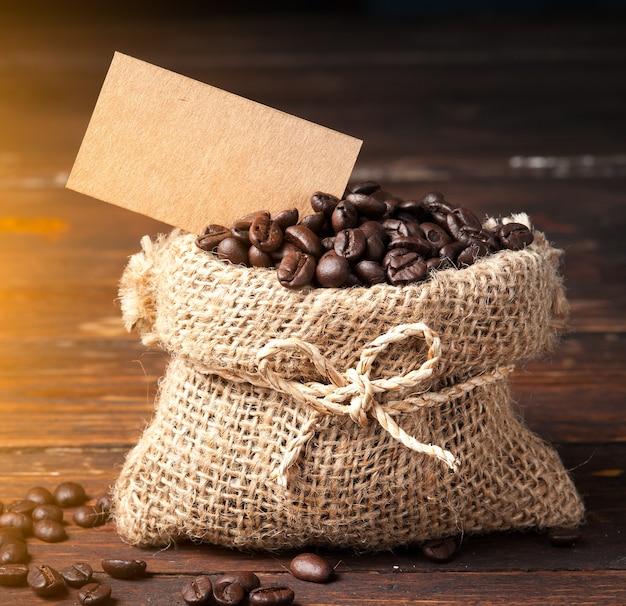 Chicchi di caffè in sacchetto e carta nota per il testo