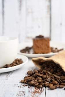 Chicchi di caffè in sacchi di canapa su una tavola di legno bianca.