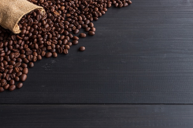 Chicchi di caffè in sacco di iuta su vecchio legno con soft-focus e più di luce in background