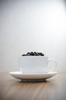 Chicchi di caffè in tazza bianca sulla tavola di legno con uso dello spazio della copia per fondo