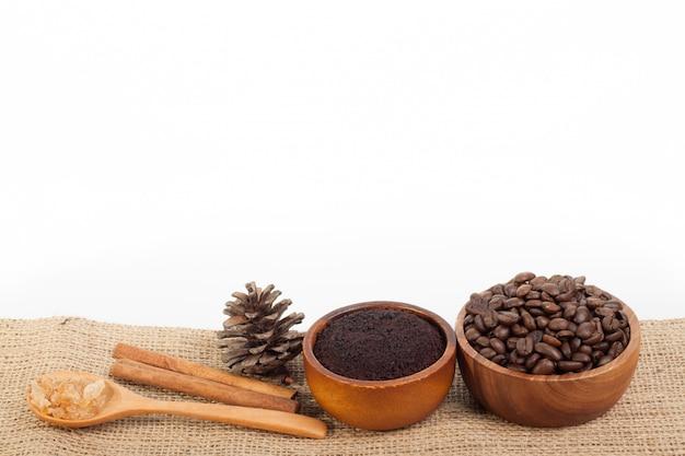 Chicchi di caffè in tazza di legno su tela da imballaggio isolata su fondo bianco