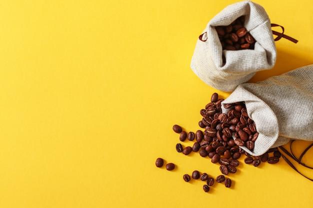Chicchi di caffè in un sacchetto di tela da imballaggio su sfondo giallo con spazio di copia per il vostro testo.