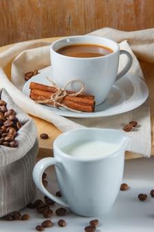 Chicchi di caffè in un sacco, latte, cannella secca e una tazza di caffè su una piattaforma e un tavolo bianco. vista laterale.