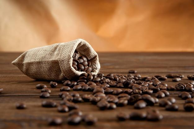 Chicchi di caffè in una piccola borsa su una tavola di legno