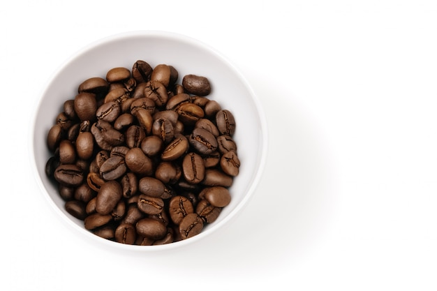 Chicchi di caffè in una tazza bianca. isolato.
