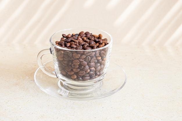 Chicchi di caffè in una tazza di vetro su una tabella.