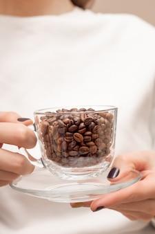 Chicchi di caffè in una tazza di vetro sulle mani femminili.