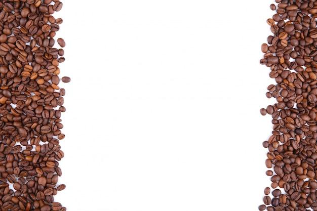 Chicchi di caffè isolati su una tavola bianca.