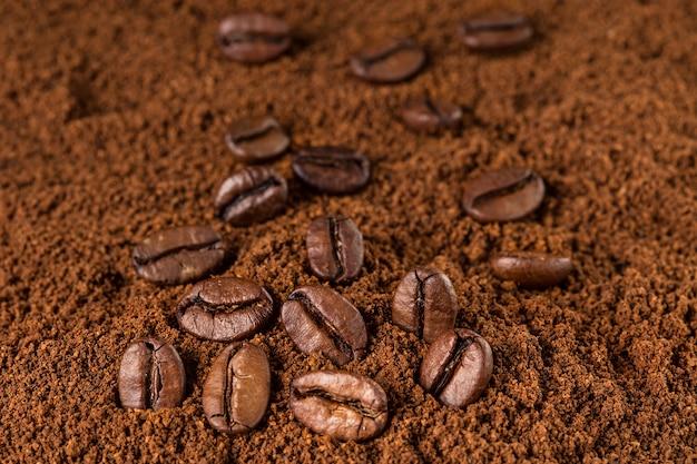 Chicchi di caffè macro sul fondo del caffè macinato