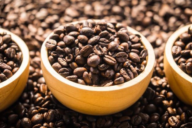 Chicchi di caffè marrone in ciotola di legno