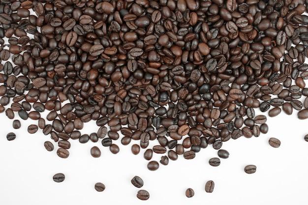 Chicchi di caffè marrone su uno sfondo bianco con spazio di copia.