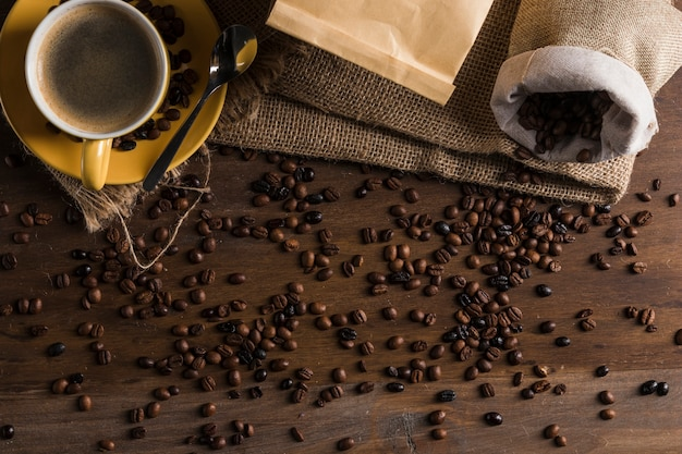 Chicchi di caffè messi sulla scrivania con sacco e tazza