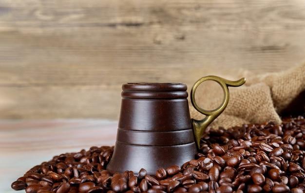 Chicchi di caffè nero con tazza di legno.