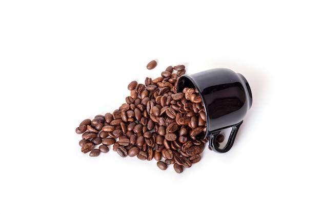 Chicchi di caffè rovesciati dalla tazza di ceramica nera isolata