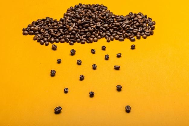 Chicchi di caffè rovesciati su un giallo luminoso