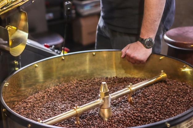 Chicchi di caffè scuri e aromatici in una moderna torrefazione