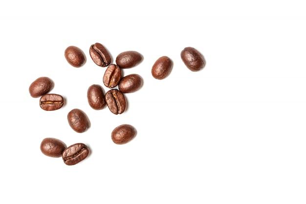 Chicchi di caffè sparsi isolati sullo spazio bianco della copia e del fondo