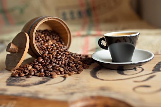 Chicchi di caffè sparsi, una tazza di caffè espresso, pezzi di cioccolato con noci su una tavola di legno.
