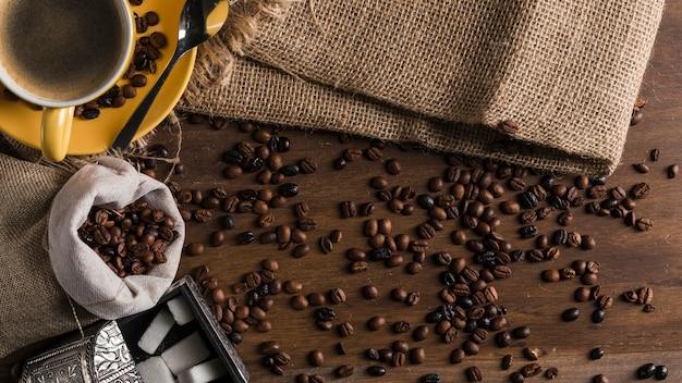Chicchi di caffè sparsi vicino a tazza, scatola di zucchero e sacco