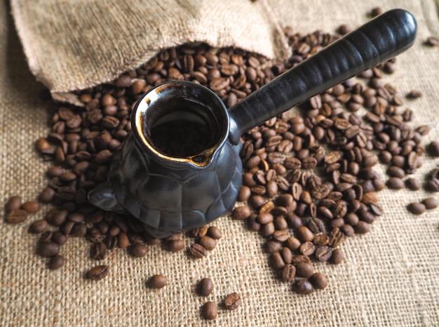 Chicchi di caffè su caffè nero tradizionale e un turco.