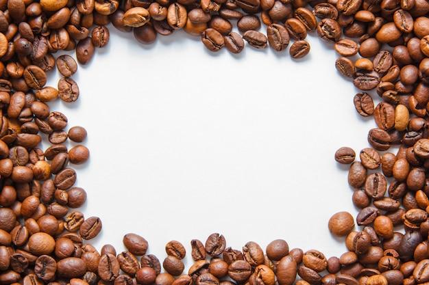 Chicchi di caffè su uno sfondo bianco. vista dall'alto. spazio per il testo