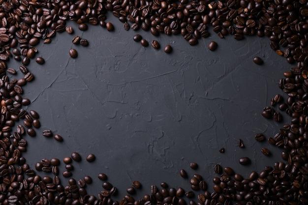 Chicchi di caffè sul vecchio beton grigio della cucina, tavola della roccia. vista dall'alto con copyspace per il testo