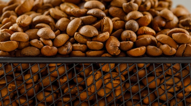 Chicchi di caffè tostati in un cestino nero su una leggera superficie bianca. vista laterale.