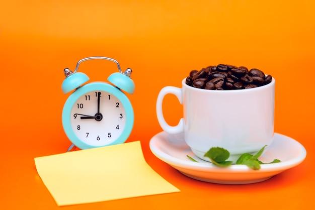 Chicchi di caffè tostati in una tazza di caffè bianco ha foglie verdi e una sveglia e su uno sfondo arancione e un adesivo per registrare