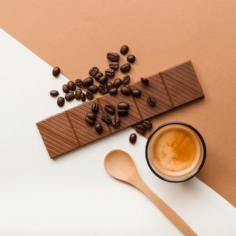 Chicchi di caffè tostati; tazza di caffè e barretta di cioccolato su doppio fondale