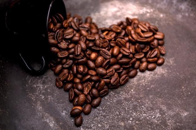 Chicchi di caffè tostato a forma di cuore.