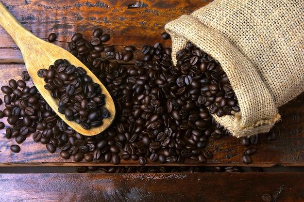Chicchi di caffè tostato e fresco all'interno del sacchetto di tessuto rustico e versato sul tavolo di legno rustico. vista dall'alto