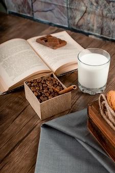 Chicchi di caffè, un bicchiere di latte e un libro