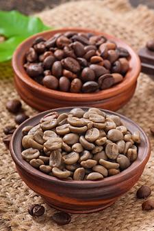Chicchi di caffè verdi e marroni in ciotole