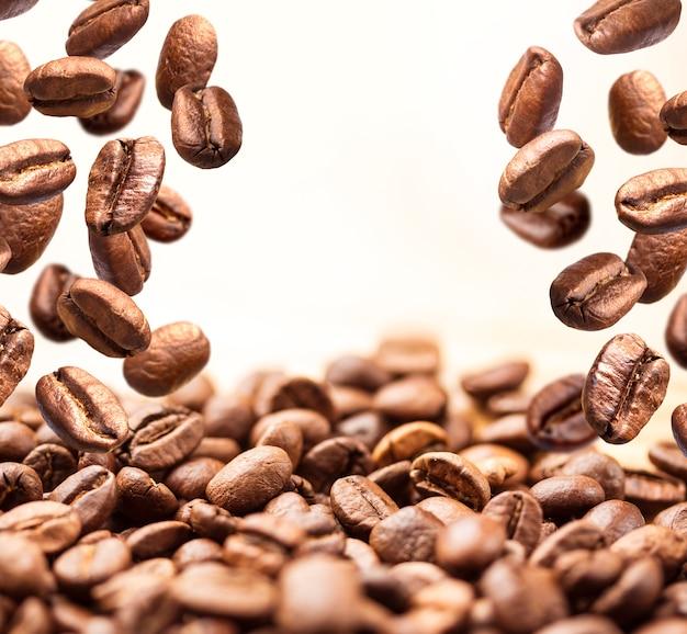 Chicchi di caffè volanti su bianco